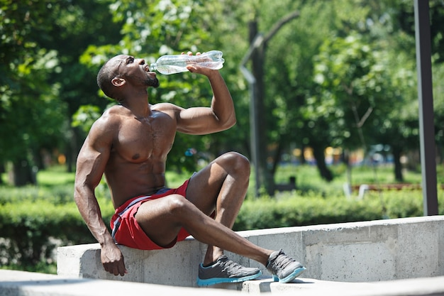 スタジアムでの運動後、休息して水を飲む健康なアスリート。街で屋外のアフロまたはアフリカ系アメリカ人の男。フィットネス、健康、ライフスタイルの概念