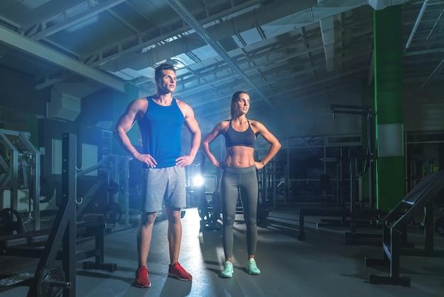 Фитнес-пара стоит в тренажерном зале на ярком светлом фоне