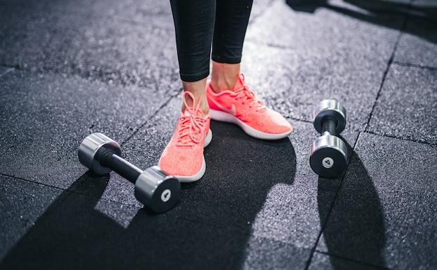ジムでダンベルを使って運動をしているフィットネスの女の子。ダンベルは床に横たわっています
