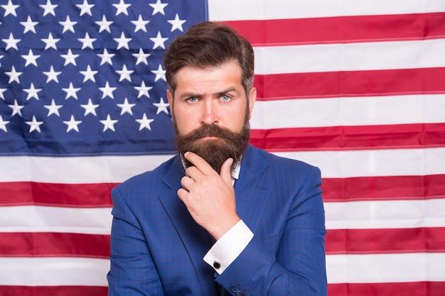 Флаг - его гордость. день независимости сша 4 июля. серьезный человек у национального флага сша. победа и свобода. образование и бизнес в америке. программа обмена студентами. американский патриотический народ.