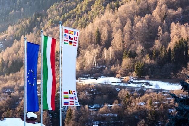 Флаг евросоюза, италии и других стран развивается на фоне доломитовых альп весной.