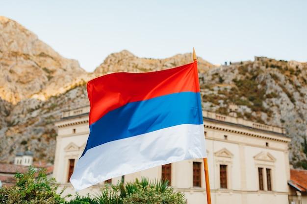 세르비아의 국기는 화창한 날에 건물과 산을 배경으로 날아갑니다.