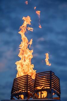Пламя исходит от газовой горелки, например от воздушного шара. на фоне темного рассветного неба.