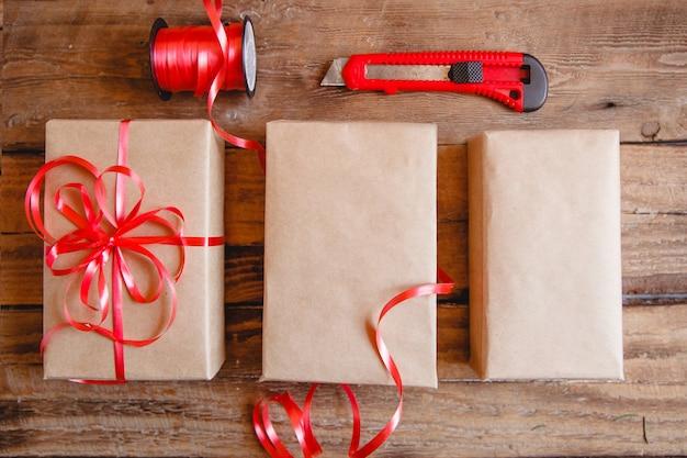 木製のテーブルにクラフトボックス、赤いリボン、赤いナイフからフラットなレイアウト。ギフトのパッケージングプロセス。