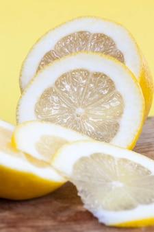 黄色いレモンの果肉をいくつかの部分にカットし、レモンは甘くてジューシーで、鋭い物体で分割されています、クローズアップ
