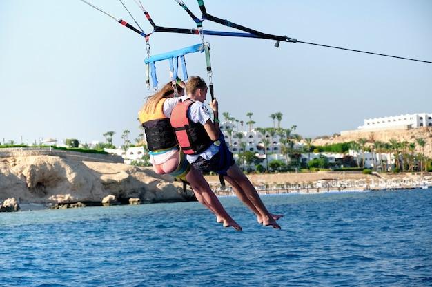Полет матери и сына на парашюте над водой. концепция активного отдыха
