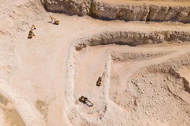 Полет дрона над карьером из песка и белого камня на изображении видны остановленные экскаваторы, вид с воздуха на каменно-песчаную промышленность