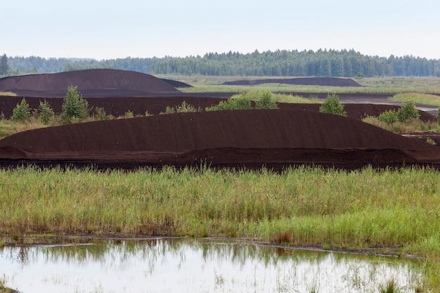 Затопленный участок, где добывается торф, черный торф укладывается огромными штабелями для погрузки на транспорт.