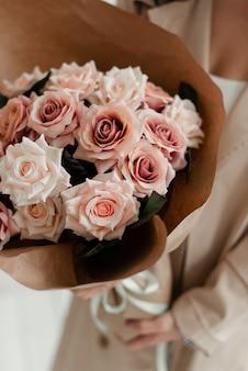 花屋はバラで作られた造花の花束を持っています。贈り物としての装飾花。花の人工花束。