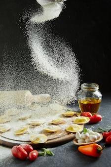 Мука попадает на равиоли. вкусные сырые равиоли с сыром и мукой, помидорами черри, подсолнечным маслом и базиликом на темном фоне.