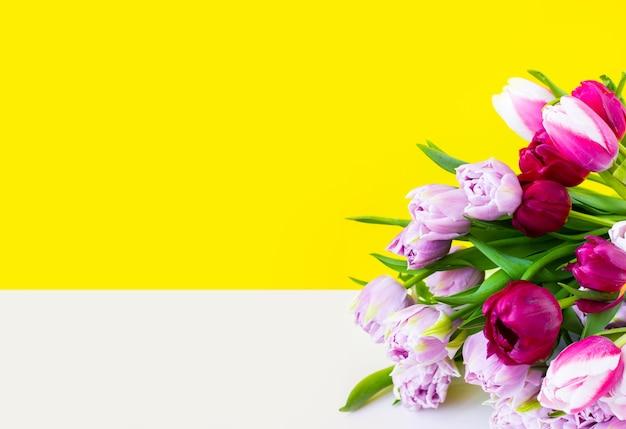 Букет цветов лежит на белом столе. фиолетовые, необычные сиреневые тюльпаны с зелеными листьями. яркий широкий баннер и место для текста