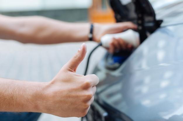 전기 자동차를 충전하는 동안 엄지 손가락을 위로 보여주는 깔끔한 남성 손에 초점