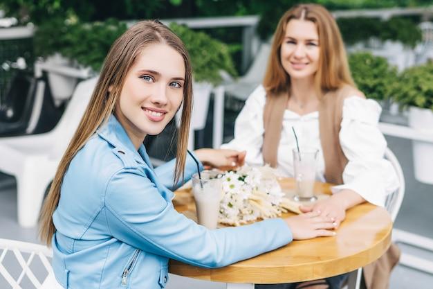 笑顔でカメラを見て、母親の手を握っている美少女に焦点を当てています