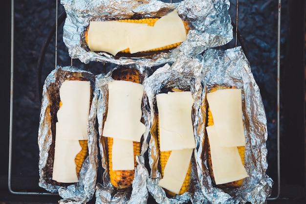 Еда на пикнике. кукуруза и сыр на гриле, завернутые в фольгу. вид сверху, над решеткой.