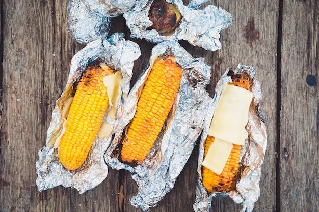 Еда на пикнике. кукуруза и сыр на гриле, завернутые в фольгу. вид сверху, на деревянном столе.