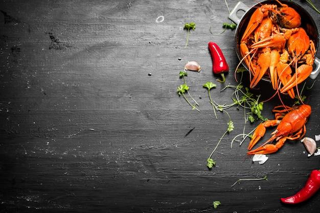 Еда деликатесов. раки отварные с зеленью и острым перцем. на черной доске.