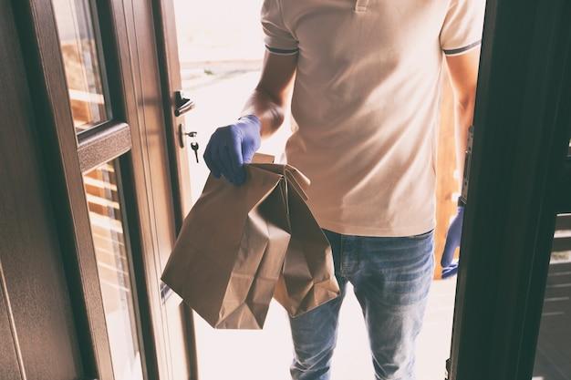 Разносчик еды в перчатках и маске отдает заказ покупателю дома