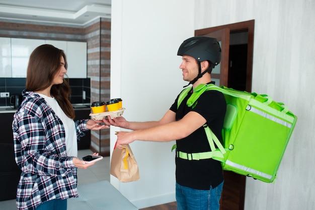 Служащий доставки еды принес кофе и бумажный пакет в дом молодой женщины. он пришел в шлеме на велосипеде или велосипеде