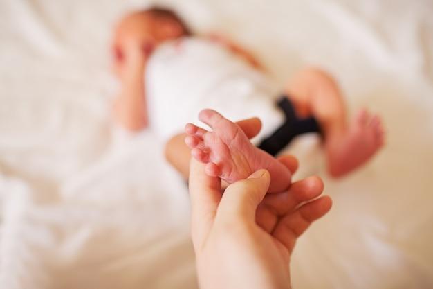 母親の手にある新生児の足。高品質の写真