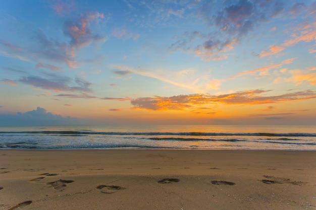 足跡は、青い空と薄明の光で海と夕日の景色の砂の上に示されました。