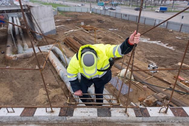 職長は建設現場の高い金属製の階段を下ります