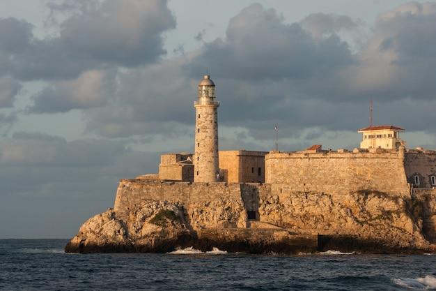 キューバのハバナ湾の入り口にあるエルモロの要塞と灯台。日没時に。