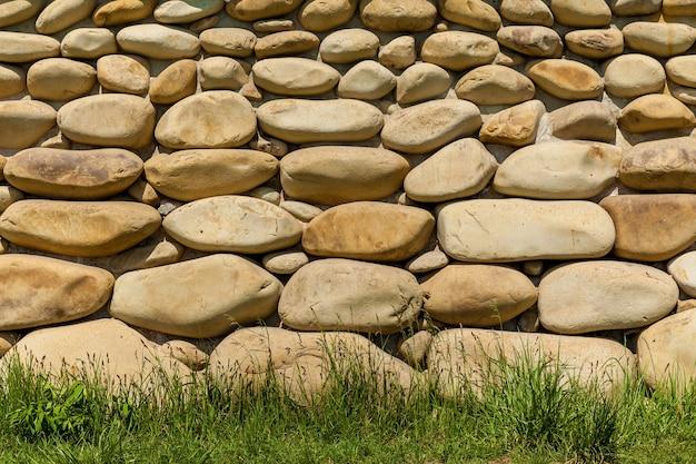 Фундамент дома украшен крупными круглыми белыми камнями. круглая каменная стена