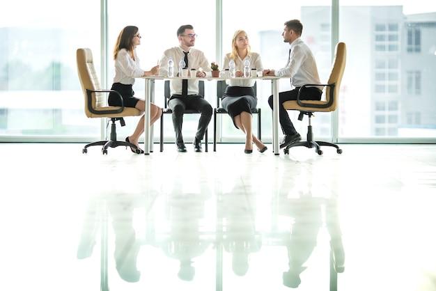 4명의 사업가들이 테이블에 앉아 토론한다