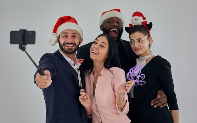 Четыре счастливых деловых человека делают рождественское селфи