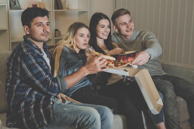 Четыре человека едят пиццу и смотрят фильм на диване.