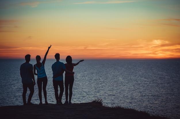 美しい夕方の空を背景に海の近くに立っている4人