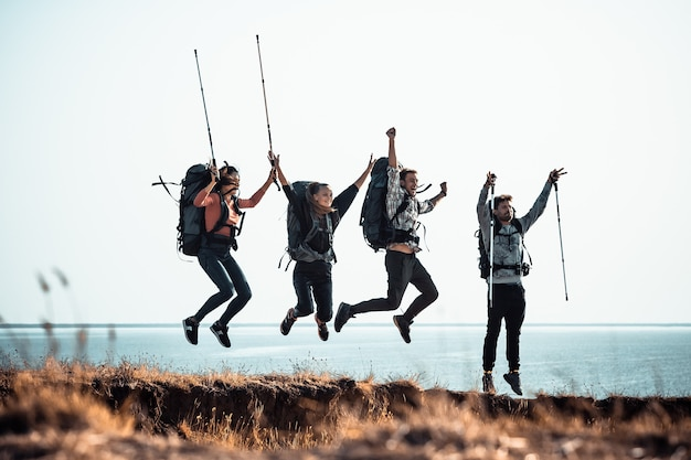 Четверо туристов с рюкзаками веселятся на берегу моря.