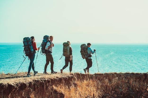 Четверо туристов с рюкзаками гуляют по берегу моря