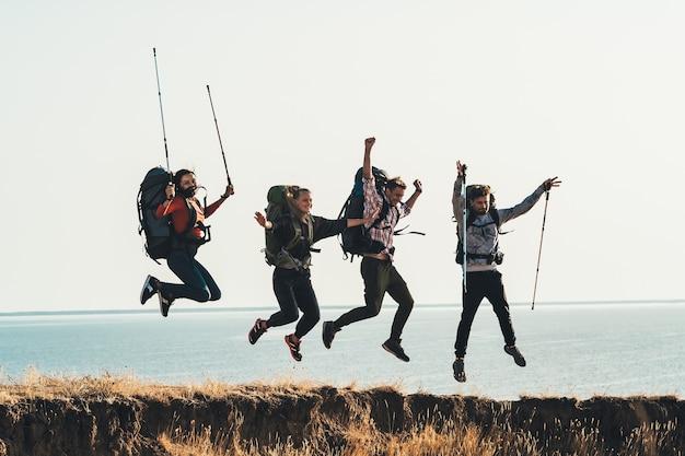 Четверо путешественников с рюкзаками веселятся на берегу моря.