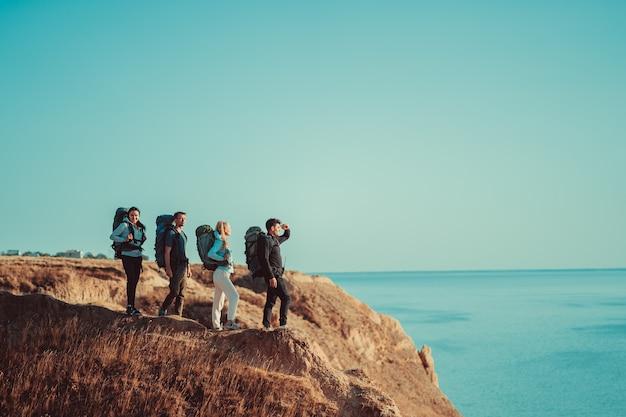 Четверо путешественников с рюкзаками стоят на вершине горы над морем.