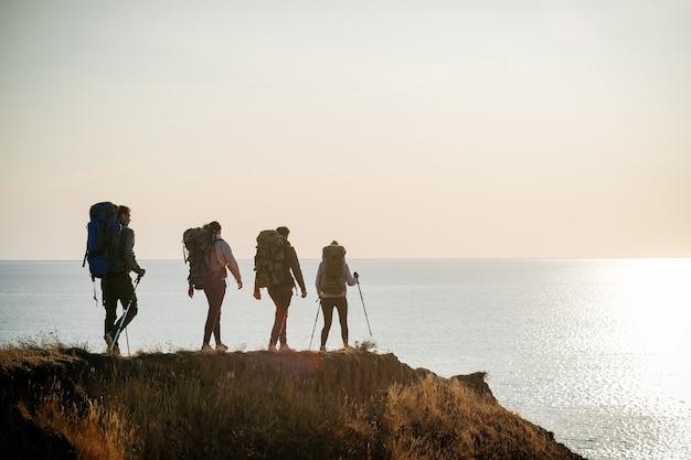 Четверо путешественников с рюкзаками гуляют на вершине горы у моря