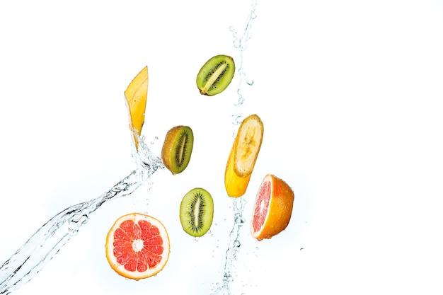 Свежие фрукты, падающие с брызгами воды, изолированные на белом фоне