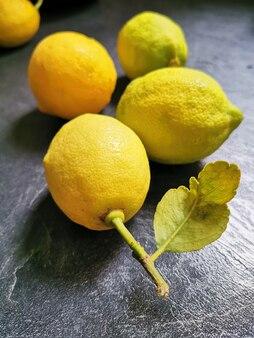 Свежие лимоны на кухонном столе из черного камня. вид сверху с копией пространства, плоская планировка.