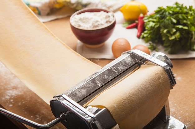 Свежая паста и машина на кухонном столе