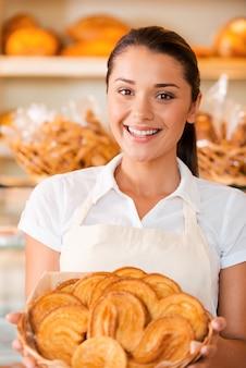 Самая свежая выпечка для наших клиентов. красивая молодая женщина в фартуке, держащая корзину с выпечкой, стоя в пекарне