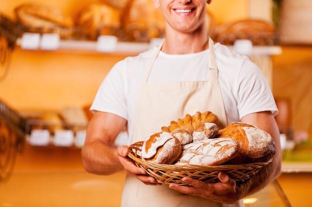 Самый свежий хлеб для вас. обрезанное изображение молодого человека в фартуке, держащего корзину с выпечкой и улыбающегося, стоя в пекарне