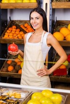 Самые свежие фрукты в городе. красивая молодая женщина в фартуке держит гранат и улыбается, стоя в продуктовом магазине с разнообразными фруктами на заднем плане