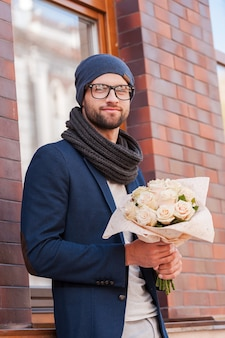 彼女にとって最も新鮮なバラ。花の花束を保持し、通りに立っている間笑顔のスマートカジュアルウェアのハンサムな若い男