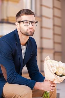 彼女にとって最も新鮮なバラ。花の花束を保持し、屋外のベンチに座って目をそらすスマートジャケットのハンサムな若い男
