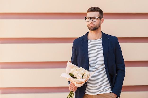 彼女にとって最も新鮮なバラ。花の花束を保持し、屋外に立っている間目をそらすスマートジャケットのハンサムな若い男