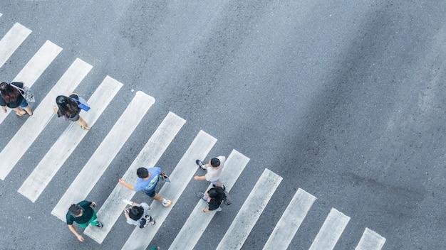Сверху крестообразный вид людей, идущих по улице, пешеходный перекресток на городской улице, вид с высоты птичьего полета.