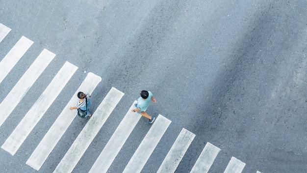 Сверху крестообразный вид людей, идущих по улице, пешеходный перекресток