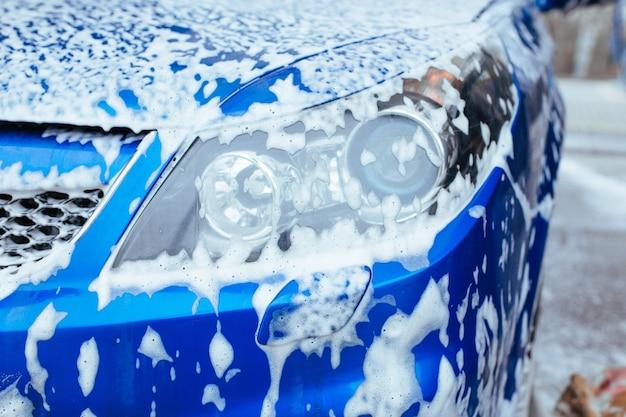 Передняя фара автомобиля покрыта мыльной пеной. автомойка самообслуживания