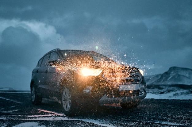 Фронтальное изображение автомобиля, фары на слегка заснеженной трассе на фоне вечернего облачного неба и гор. покупка, аренда авто. путешествия, туризм и отдых.