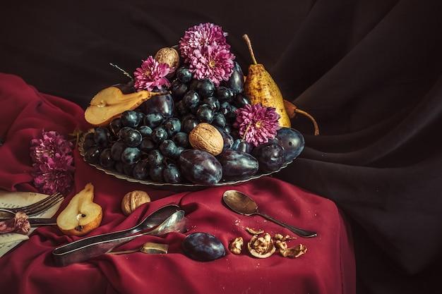 あずき色のテーブルクロスに対してブドウとプラムのフルーツボウル